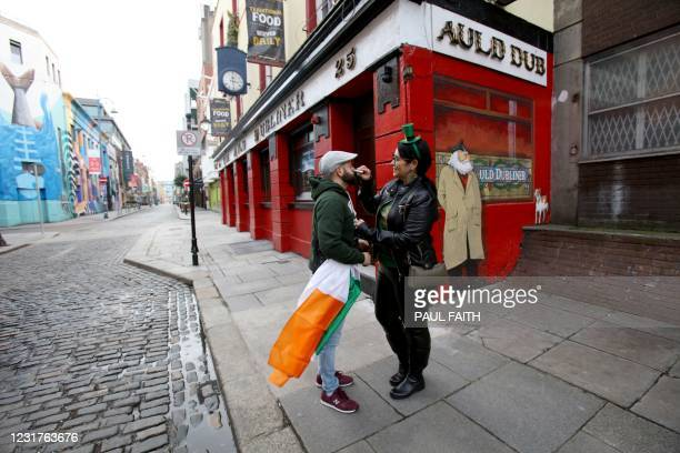 People pose for pictures on St Patrick's Day in Dublin on March 17 as official St Patrick's Day celebrations have been cancelled for the second year...