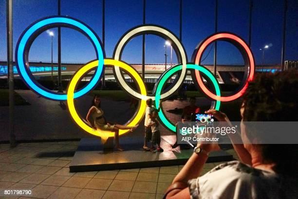 People pose for pictures with the Olympic rings left behind from the 2014 Winter Olympics in Sochi on June 26 2017 on the sidelines of the 2017 FIFA...
