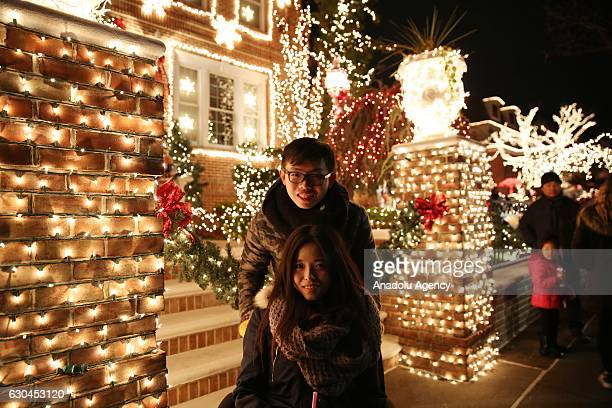People pose in front of houses decorated with christmas lights in Dyker Heights neighbourhood in Brooklyn, USA, on December 21, 2016.