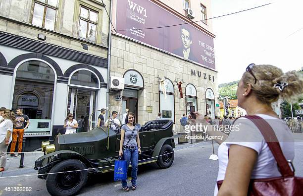 People pose in front of the museum where displayed the assassination of Archduke Franz Ferdinand of Austria and his wife Duchess Sophie by Serbian...