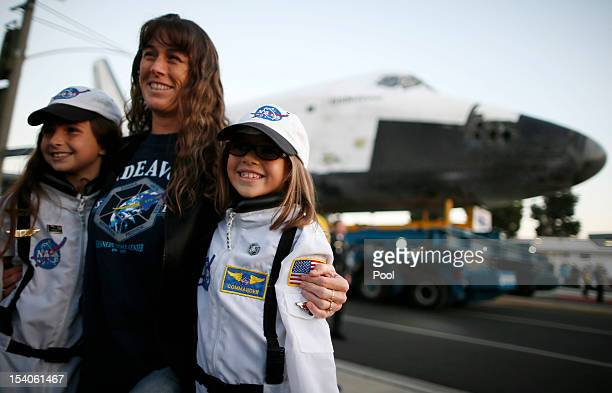 People pose in NASA suits in front of the Space Shuttle Endeavour as it is moved to the California Science Center on October 13 2012 in Inglewood...