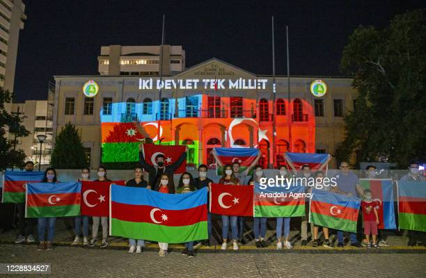People pose with flags as the flags of Azerbaijan and Turkey are projected on the governor's building n order to show solidarity with Azerbaijan in...