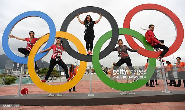 TOPSHOT People pose with the Olympic rings at the Olympic Park in Rio de Janeiro on August 3 ahead of the 2016 Rio Olympic Games / AFP / Kirill...