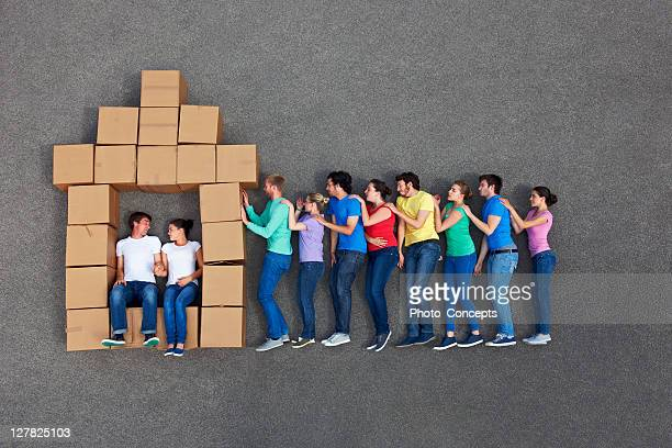 People posing by cardboard box house