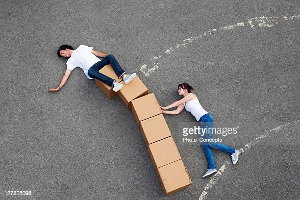 people posing with cardboard boxes - optical illusion stock photos and pictures
