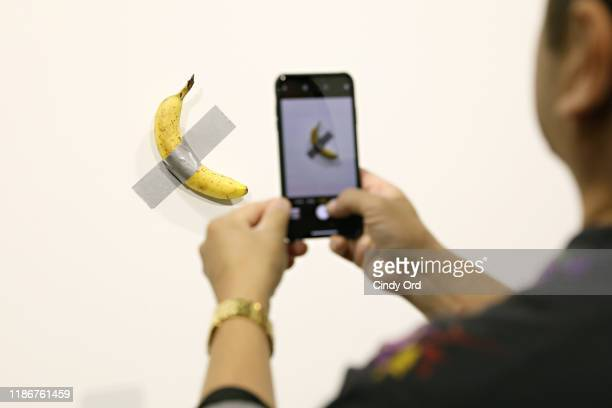 People post in front of Maurizio Cattelan's Comedian presented by Perrotin Gallery and on view at Art Basel Miami 2019 at Miami Beach Convention...