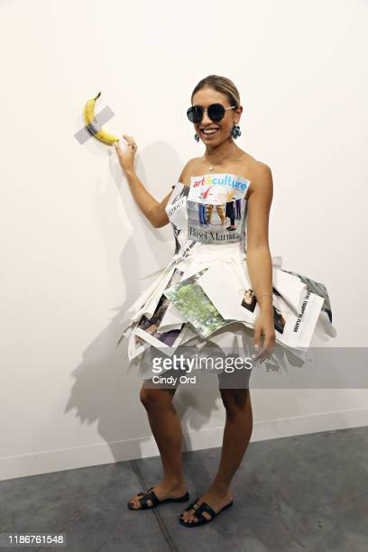 """People post in front of Maurizio Cattelan's """"Comedian"""" presented by Perrotin Gallery and on view at Art Basel Miami 2019 at Miami Beach Convention..."""
