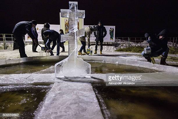 People pour consecrated water from the Tura River into plastic bottles on Epiphany night January 19 2016 in Tyumen Siberia Russian Orthodox celebrate...