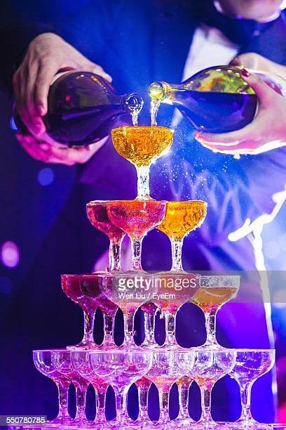 People Pouring Champagne In Glass Pyramid