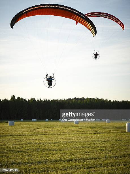 People Powered Paragliding Over Grassy Field
