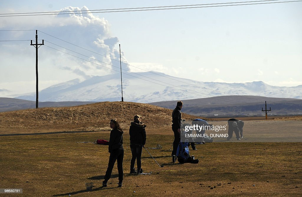 People practice golf as smoke and ash billow from Eyjafjallajokull volcano as it is seen from Hvolsvollur, Iceland, on April 23, 2010. Ash from a volcano in Iceland which caused Europe to lock down its skies forced the country's main airport to shut Friday, as tourism chiefs said the crisis had cost the industry 1.7 billion euros. AFP PHOTO/Emmanuel Dunand