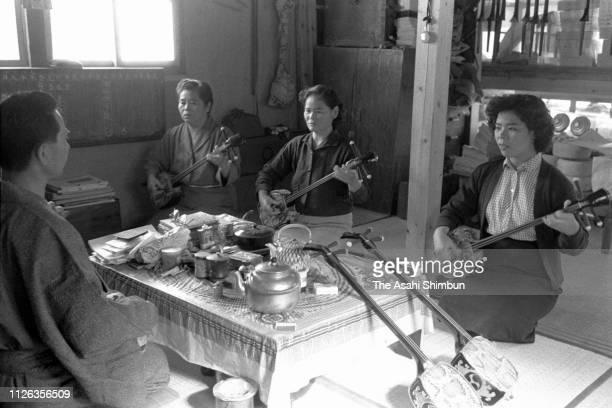 People practice Sanshin circa October 1957 in Makishi, Okinawa, Japan.
