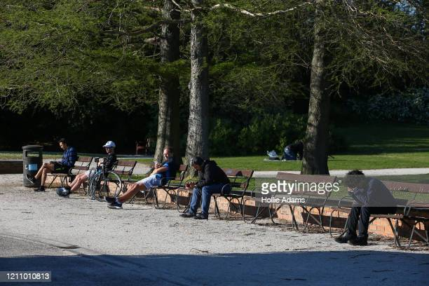 People practice social distancing while sitting in Battersea Park on April 25 2020 in London United Kingdom The British government has extended the...