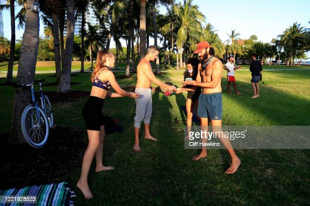 People practicing slacklining and acroyoga share alcohol based sanitizer in South Pointe Park on April 29 2020 in Miami Beach Florida The city of...