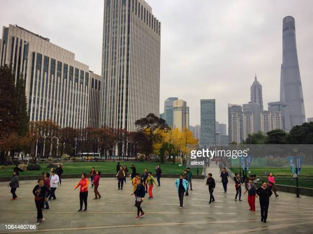 People practicing tai in Shanghai China background modern skyscrapers skyline urban city