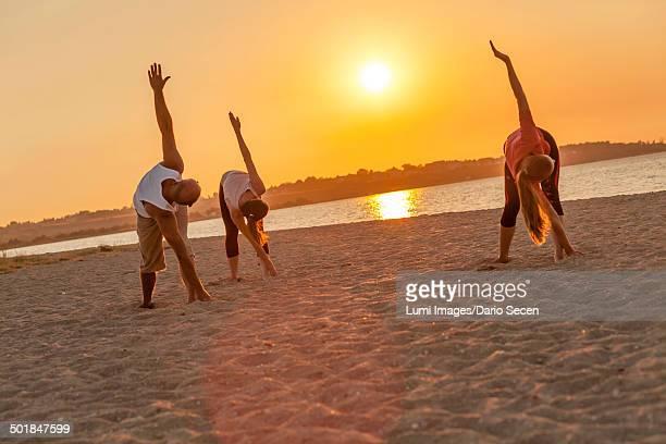 People practicing yoga on beach, bending over