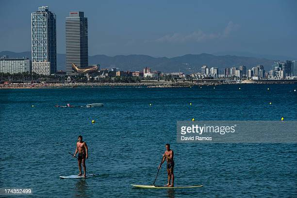 People practise stand up paddle surf at Barceloneta Beach on July 24 2013 in Barcelona Spain Foreign visitors to Spain set a new record high in June...
