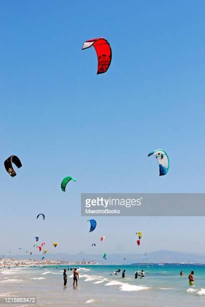 gente practicando kitesurfing en la playa de tarifa en el sur de españa - cádiz fotografías e imágenes de stock