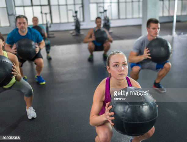 people praticising in gym with medicine ball - medicine ball stock pictures, royalty-free photos & images