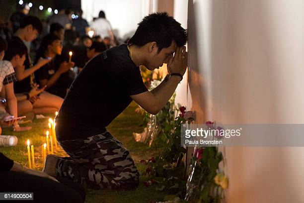 People pray and light candles in memory of the late King of Thailand outside the Grand Palace in the early hours of October 16 2016 in Bangkok...