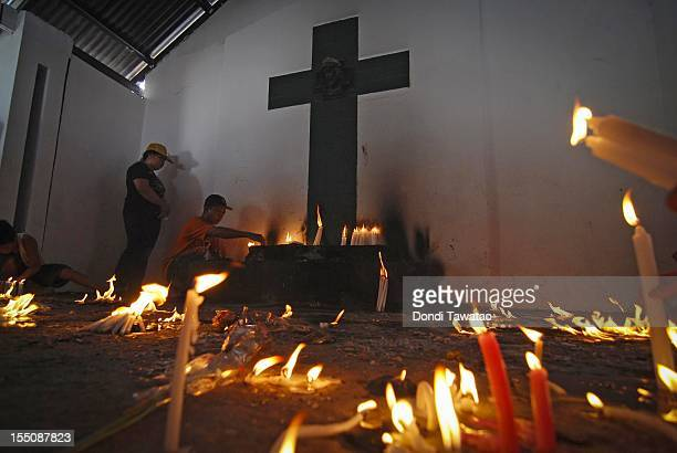 People pray and light candles on tombstones of the departed at the Navotas public cemetery on November 1 2011 in Manila Philippines The 'Day of the...