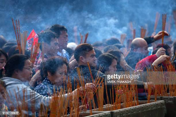 People pray and make offerings with incense sticks during Lunar New Year celebrations for the Year of the Dog at the Wong Tai Sin temple in Hong Kong...