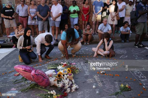 People pray and mourn at an informal memorial at the place where 32yearold Heather Heyer was killed when a car plowed into a crowd of people...