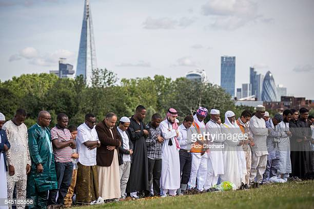 People pray as they celebrate the festival of Eid at Southwark Eid Festival in Burgess Park on July 6 2016 in London England Thousands gathered at...