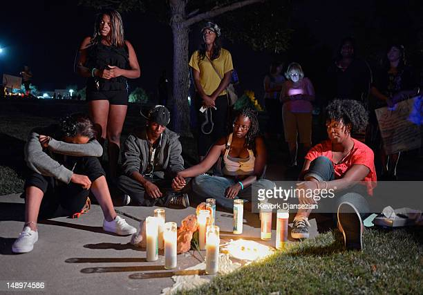 People pray at a makeshift memorial during a vigil for victims of Century 16 movie theatre where a gunmen attacked movie goers during an early...