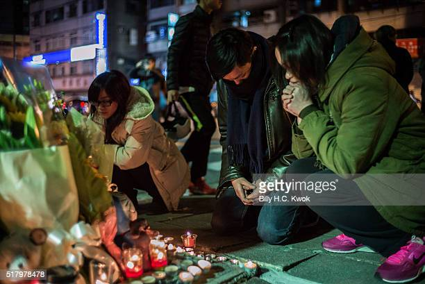 People pray at a makeshift memorial where a girl was found decapitated by a knifewielding assailant outside a subway station on March 28 2016 in...