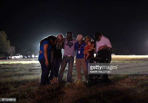 People pray at a vigil after a mass shooting that killed 26 people in Sutherland Springs Texas on November 6 2017 A gunman wearing all black armed...
