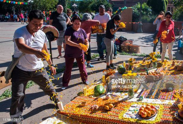 People pray at an altar during the Dia De Muertos celebration in Los Angeles on October 26 2019 The traditional Mexican holiday is believed to date...