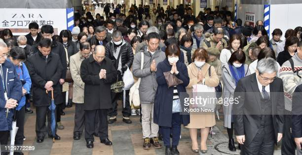 People pray at an arcade in Sendai Miyagi Prefecture at 246 pm on March 11 the eighth anniversary of the devastating earthquake and tsunami in...