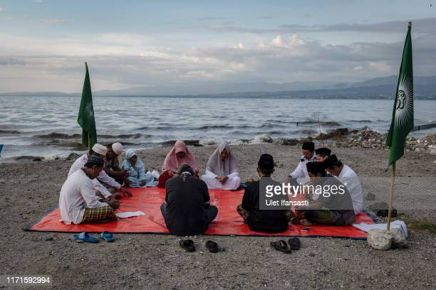 People pray at Talise beach that was hit by the earthquake and tsunami during Indonesians mark one year since the Palu earthquake on September 28,...