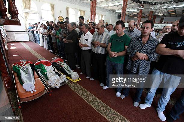 People pray at the funeral of three Palestinians on August 262013 at the Qalandia Refugee Camp near Ramallah Palestine The 3 Palestinians died during...