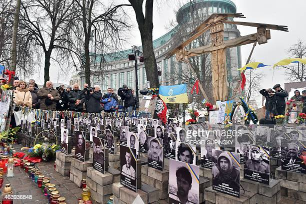 People pray at the 'Heavenly Hundred' monument set for killed Maidan activists in Kiev on February 20 during memorial ceremony marking the first...