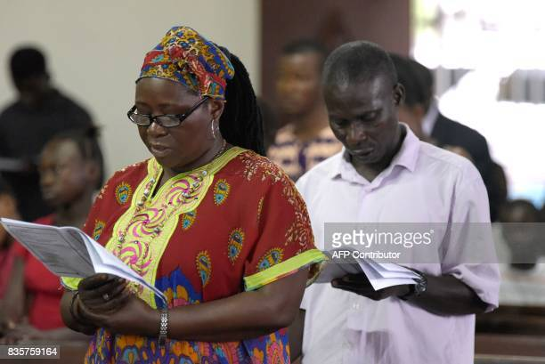 People pray at the Saint Paul Catholic Church in Freetown days after the partial collapse of a hillside that swept away hundreds of homes in a...