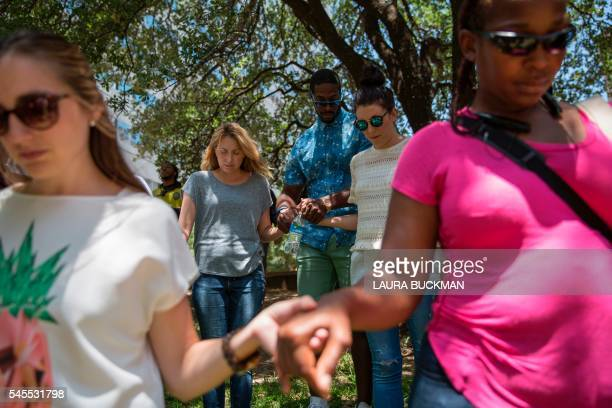 TOPSHOT People pray during a faith vigil at ThanksGiving Square in Dallas Texas on July 8 following the shootings during a peaceful protest on July 7...