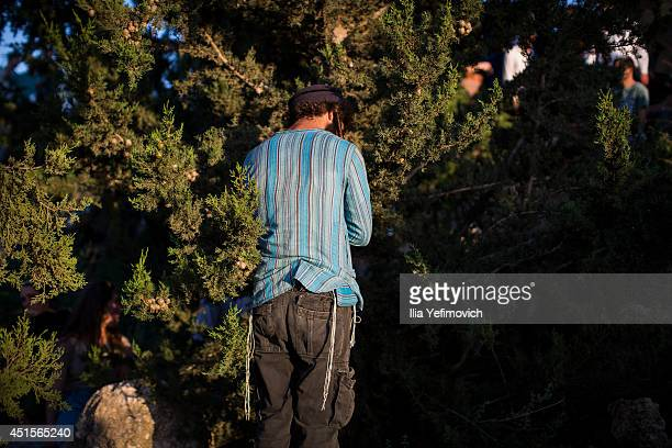 People pray during the funeral ceremony held for the three Israeli teenagers found dead on July 1 2014 in Modiin Israel The bodies of Eyal Yifrah...