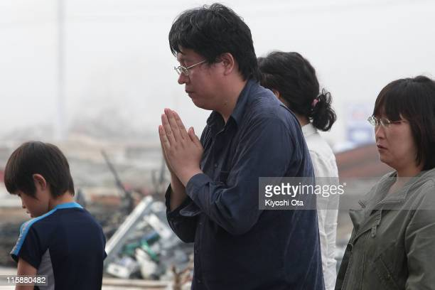 People pray for the earthquake and tsunami victims on June 11 2011 in Minamisanriku Miyagi Japan Japanese government has been struggling to deal with...