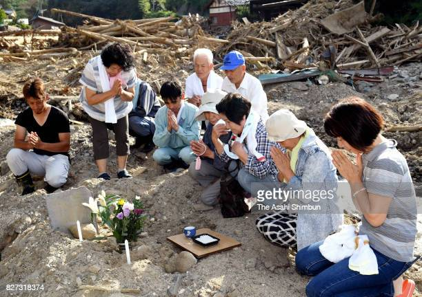 People pray for the victims a month after the mudslide triggered by torrential rain on August 5 2017 in Asakura Fukuoka Japan