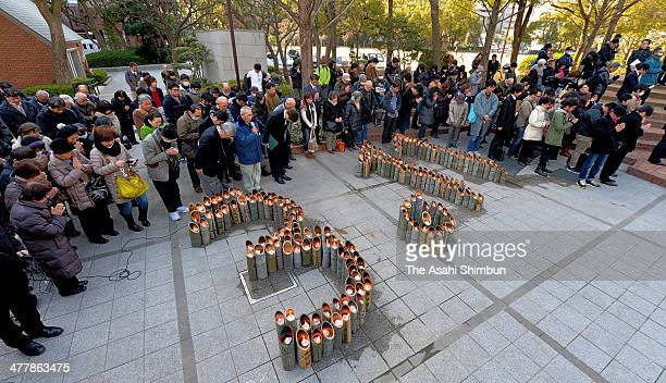 People pray for the victims at 246pm during a memorial ceremony at HIgashi Yuenchi Park on March 11 2014 in Kobe Hyogo Japan Japan marks the third...