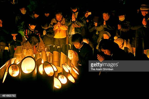 People pray for the victims in front of the candlelit bamboo lanterns to mark the 20th anniversary at Higashi Yuenchi Park on January 17 2015 in Kobe...