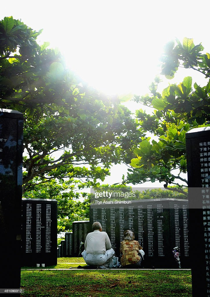 People pray for the victims in front of the Cornerstone of Peace memorial at the 'Mabuni-no-oka', in Peace Memorial Park as Japan marks the 69th anniversary of the end of the 'Battle of Okinawa' on June 23, 2014 in Itoman, Okinawa, Japan. This year, an additional 54 people were added to the Cornerstone of Peace memorial on which is engraved the names of those who died in the Battle of Okinawa. There are now a total of 241,281 military and civilian names etched in the monument, including soldiers from both Japan and the United States.