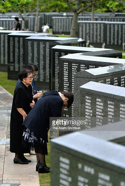 People pray for the victims in front of the Cornerstone of Peace memorial at the 'Mabuni-no-oka', in Peace Memorial Park as Japan marks the 69th...