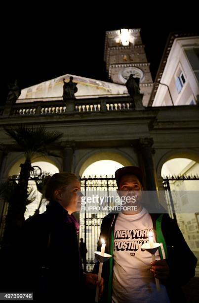 People pray for the victims of Paris attacks outside Santa Maria in Trastevere Basilica in Rome on November 16 2015 Islamic State jihadists claimed a...