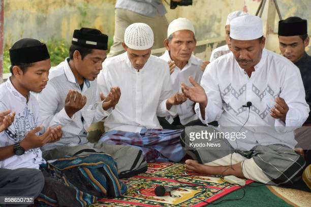 People pray for the victims of the 2004 earthquaketsunami disaster off Sumatra Island in Indonesia's Aceh province on Dec 26 the 13th anniversary of...