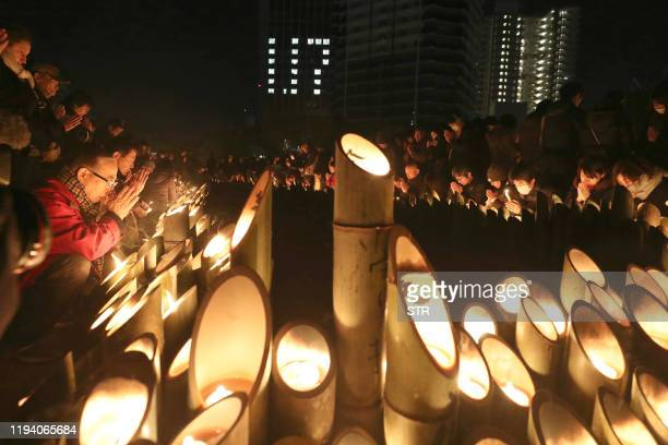 People pray for victims around candles commemorating the 25th anniversary of the Great Hanshin earthquake at a park in Kobe, Hyogo prefecture on...