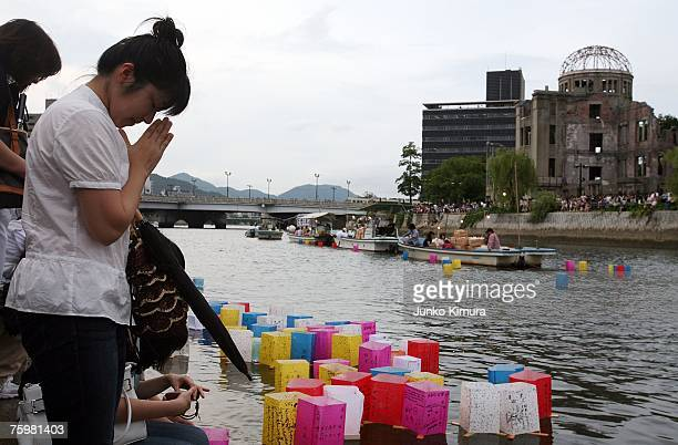 People pray for world peace at the banks of Motoyasu river in front of the Atomic Bomb Dome in memory of the victims of the bomb on the 62nd...