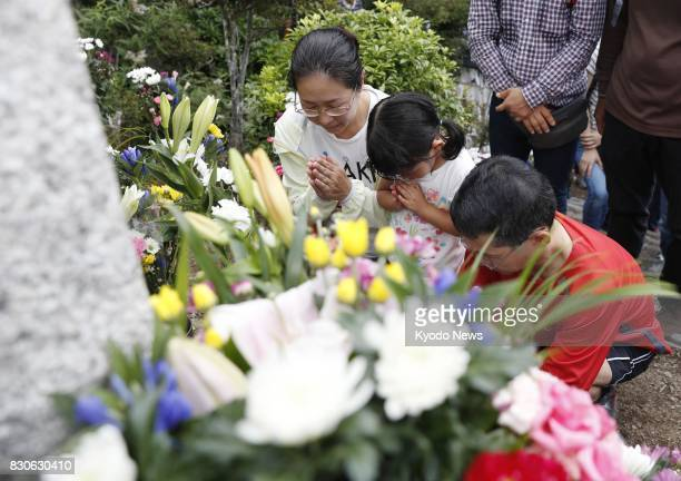 People pray in front of a cenotaph on Osutaka Ridge atop a mountain in Gunma Prefecture northwest of Tokyo on Aug 12 the 32nd anniversary of the...